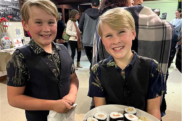 Boys serving sushi